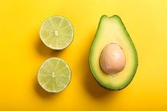 Kalk und Avocado auf gelbem Hintergrund Lizenzfreie Stockfotografie
