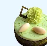 Kalk- und Pistazienkuchen mit Schokoladendekorationen mit grüner Gartennelkenblume lizenzfreie stockfotografie