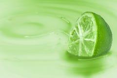 Kalk untergetaucht in einer hellgrünen Flüssigkeit mit der Übereinstimmung von Milch Stockfotos
