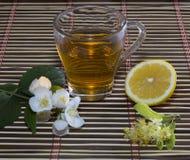 Kalka te, citronen och blomman på en dekorativ filt Arkivbild
