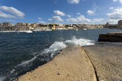 Kalkara Malta. An old village in the Grand Harbour, Malta. Water spray from the splashing waves from the sea in winter Royalty Free Stock Image