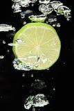 Kalken Sie (Zitrone) das Fallen in Wasser auf Schwarzem Lizenzfreies Stockfoto