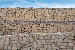 Kalksteen gelaagd, ruwe droge steenmuur, onder een blauwe hemel stock afbeeldingen