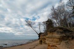 Kalksteenstrand bij de Oostzee met mooi zandpatroon en levendige rode en oranje kleur - Toeristengeschrift op stock afbeelding