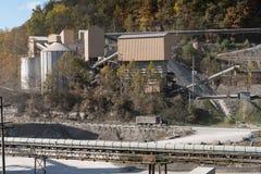 Kalkstein oder zerquetschte Steinfabrik in bewaldetem Tal Lizenzfreie Stockfotos