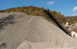 Kalkstein oder zerquetschte Steinfabrik in bewaldetem Tal Stockbild