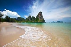 Kalksteinklippen des Krabi Schachtes einen Strand übersehend Lizenzfreie Stockfotos