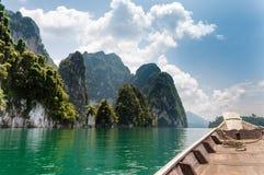Kalksten vaggar och det Longtail fartyget på Cheow Lan Lake, Thailand arkivfoton