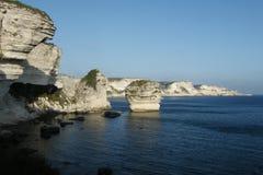 Kalkstenklippor som ses från Bonifacio med den Pertusato fyren Korsika ö, Frankrike arkivbilder