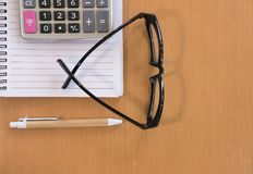 kalkulator, ballpoint pióro, pusty notatnik, eyeglasses na biurze Obrazy Stock