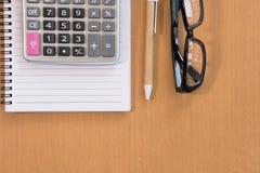 kalkulator, ballpoint pióro, pusty notatnik, eyeglasses na biurze Zdjęcie Royalty Free