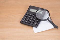 Kalkulator i magnifier w badawczym pojęciu zdjęcia stock