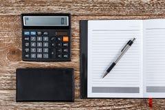 Kalkulator i notatnik dla biznesu egzaminu próbnego up na drewnianym backgroun Zdjęcia Stock