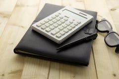 Kalkulator i notatnik na biurku Zdjęcia Royalty Free