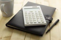 Kalkulator i notatnik na biurku Fotografia Stock