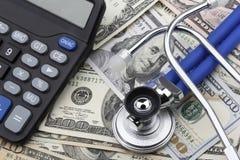 Kalkulator i stetoskop na górze dolarów amerykańskich banknotów (USD) Zdjęcie Stock