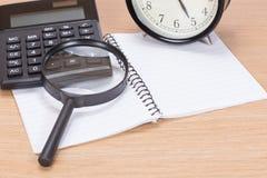 Kalkulator, magnifier, zegar i pustego miejsca notepad, obrazy stock