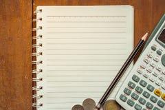 Kalkulator, moneta, noteboook i ołówek na drewnianym, Obrazy Stock