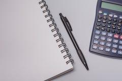 Kalkulator, notatnik i pióro na biurowym stole na białym tle, budżeta burlap monet pojęcia dziura jadący worek rozlewający Obraz Stock