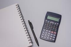 Kalkulator, notatnik i pióro na biurowym stole na białym tle, budżeta burlap monet pojęcia dziura jadący worek rozlewający Fotografia Stock