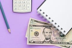 Kalkulator, notatnik z amerykańskim pieniądze i ołówek na lilym tle, zdjęcie royalty free