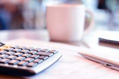 Kalkulator & pióro nad papierem na stole z plamy filiżanki tłem Zdjęcie Royalty Free