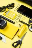 Kalkulator, smartphone i szkolne dostawy na kolorze żółtym, Fotografia Stock