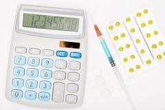 Kalkulator, strzykawka i pigułki na popielatym tle, Fotografia Stock