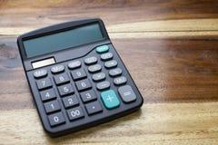 Kalkulator z drewnianym stołowym tłem Obraz Stock