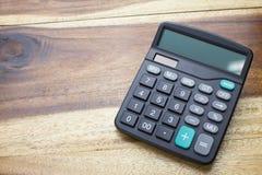Kalkulator z drewnianym stołowym tłem Obrazy Royalty Free