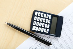 Kalkulator z piórem na drewnianym tle Fotografia Stock