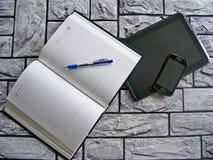 Kalkulatora, pióra, smartphone i książki agenda na ściana z cegieł tle, Obrazy Stock