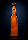 Kall ölflaska med droppar, på black Arkivfoton