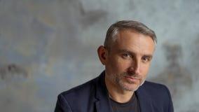 Kall affärsman med grått hår och skägg på grå bakgrund royaltyfri foto