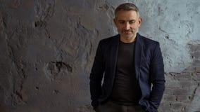 Kall affärsman med grått hår- och skägganseende på grå bakgrund royaltyfria foton