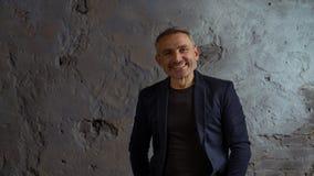 Kall affärsman med grått hår- och skägganseende på grå bakgrund arkivfoto