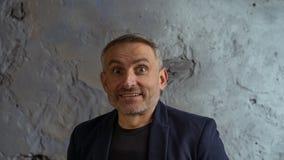 Kall affärsman med grått hår- och skägganseende på grå bakgrund royaltyfri bild