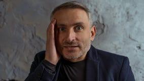 Kall affärsman med grått hår- och skägganseende på grå bakgrund fotografering för bildbyråer