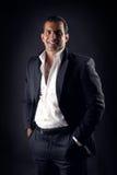 Kall affärsman som poserar mot en svart bakgrund Royaltyfri Fotografi