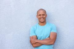 Kall afrikansk amerikanman som ler med korsade armar arkivfoton