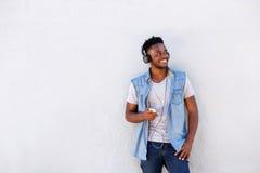 Kall afrikansk grabb med mobiltelefonen och hörlurar som lyssnar till musik royaltyfri bild