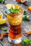 Kall alkoholiserad coctail med cola, is, mintkaramellen och citronen i exponeringsglas på träbakgrund Sommardrinkar Royaltyfri Bild