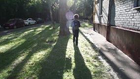 Kall blandad pojke som förutom går hans hus efter skola arkivfilmer