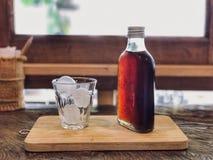 Kall brygdkaffeflaska och is på exponeringsglas på trämagasinet och trä arkivfoto