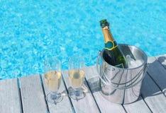 Kall champagneflaska i ishink och två exponeringsglas av champagne på däcket vid flaskan i hink och två exponeringsglas av champa Fotografering för Bildbyråer