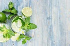 Kall detoxsommarmineralvatten med limefrukt, mintkaramell, is, sugrör på mjuk blå wood bakgrund som den dekorativa gränsen, bästa arkivfoto