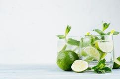 Kall detoxsommarmineralvatten med limefrukt, mintkaramell, is, sugrör på mjuk vit bakgrund, kopieringsutrymme royaltyfri foto