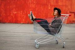 Kall flicka för modehipster i shoppingvagnen som har gyckel mot th fotografering för bildbyråer