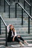 Kall flicka för modehipster i solglasögon stads- bakgrund, modeblick Modellsammanträde på trappan Arkivfoto