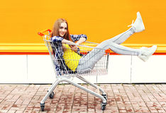 Kall flicka för mode som har roligt sammanträde i shoppingspårvagnvagn Fotografering för Bildbyråer